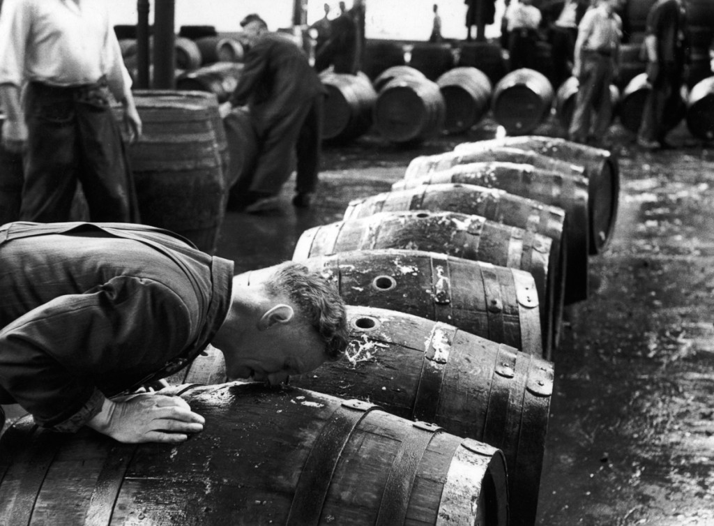 A 'smeller' sniffs scalded casks to check their cleanliness, at the Guinness brewery at St. James's Gate, Dublin, 22nd August 1953. Original publication: Picture Post - 6666 - Ireland's National Drink - pub. 1953 (Photo by Bert Hardy/Picture Post/Hulton Archive/Getty Images)