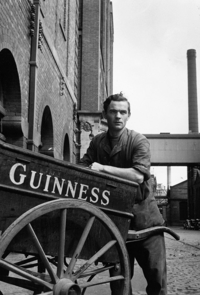 22nd August 1953: Eugene Hackett, a worker at the Guinness brewery on the banks of the Liffey at St James' Gate, Dublin, leaning on a barrow which is used to take malt samples from one part of the brewery to another. Four-fifths of Ireland's beer is brewed at this site. Original Publication: Picture Post - 6666 - Ireland's National Drink - pub. 1953 (Photo by Bert Hardy/Picture Post/Getty Images)